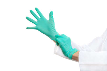 Doctor puts on surgical gloves, isolated over white background photo