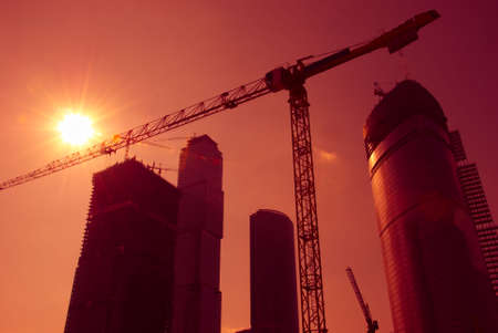 Sky-scrapers construction. Cranes and buildings over red sky.   photo