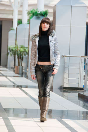 Thin girl walking in a shopping centre photo