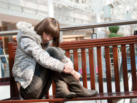Sad young girl sits on a bench in a mall photo