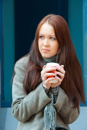 Young frozen woman with coffee on a street photo
