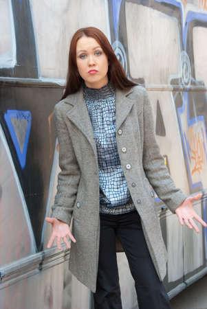swear: Aggressive woman stands near wall with graffiti Stock Photo