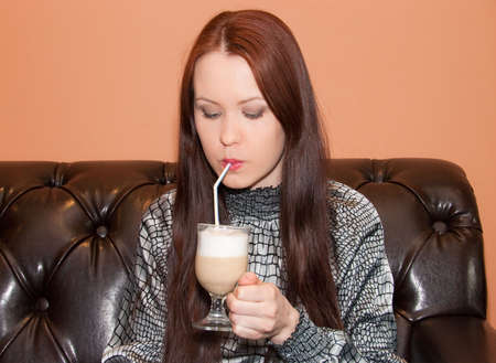 Young woman drinks latte in cafe Stock Photo - 4788496