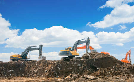 excavate: Three excavators working on a constuction site
