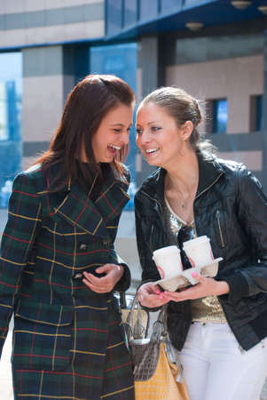 Two happy girls laughing on a street Stock Photo