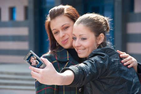 lesbian relationship: Two happy girls make self-portrait on a street