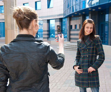 picture person: Girl take a picture of an other girl on a street by mobile phone. Focus to girl Stock Photo