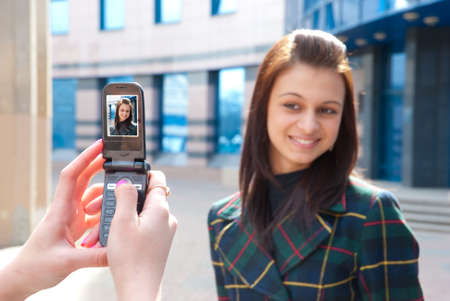 Girl take a picture of an other girl on a street by mobile phone. Focus to mobile phone   photo