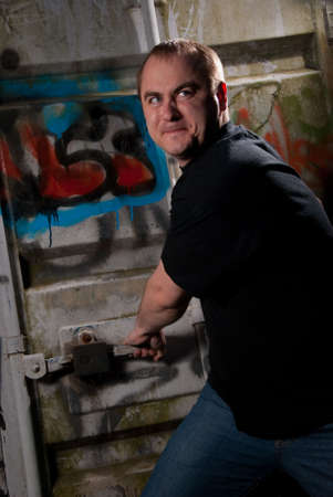 brute: Powerful man expression portrait in a dark near container with graffiti Stock Photo