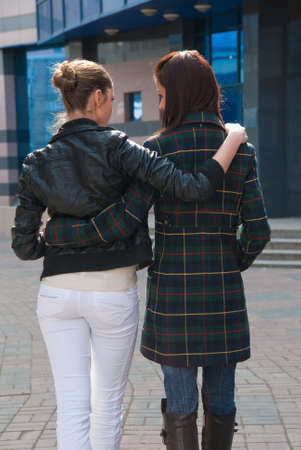 adult sisters: Two girls going embraced on a street. Back view. Stock Photo