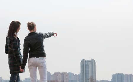 mujer mirando el horizonte: Dos muchachas j�venes que buscan una gran ciudad de panorama Foto de archivo