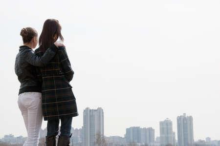 mujer mirando el horizonte: Dos chicas j�venes que buscan un panorama de la gran ciudad
