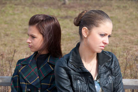 offend: Quarrel girls sit on a bench in a park Stock Photo