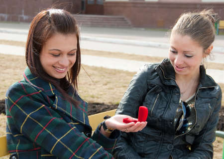 beautiful lesbian: One girl shows to other ring in red box Stock Photo