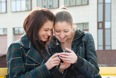 Two happy girls watch something in mobile phone Stock Photo - 4916274