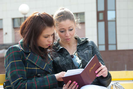 Two girls watch photos in album sitting outdoors photo