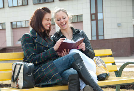 Two happy girls watch photos in album sitting on a bench outdoors Stock Photo