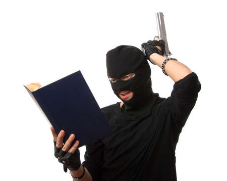 hijack: Perplexed robber with gun reads book over white. You can write funny title on the book cover. Stock Photo