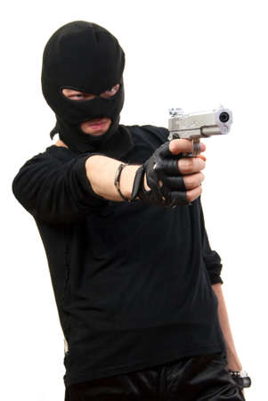 Criminal in black mask with gun isolated over white background. Focus to gun.   photo