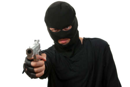 Criminal in black mask with gun isolated over white background. Focus to face.