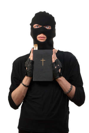 mugger: Repentant robber with the Bible isolated over white background