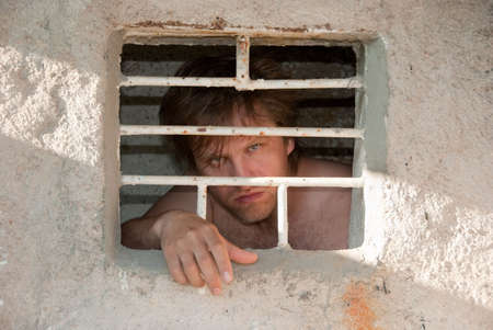 Portrait of a prisoner behind a grate Stock Photo - 5025569