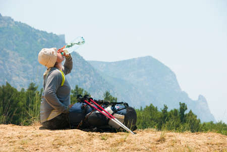 Tired hiker drinks water from a bottle photo