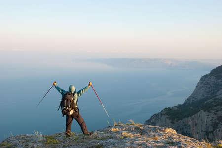 Hiker on a peak enjoys seashore landscape Stock Photo - 5025550