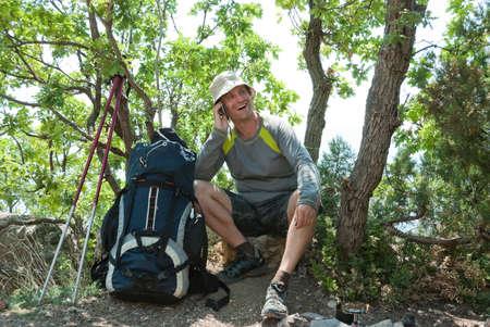 halt: Happy hiker calling home on a halt Stock Photo