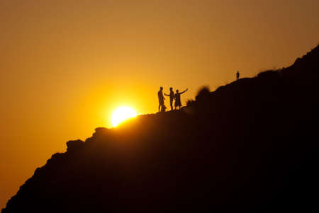 People silhouettes on a mountainside over sunset photo