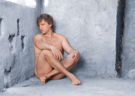 Nude man sitting in concrete interior