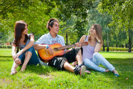 Guy playing guitar in the park, next to him sat two beautiful girls photo