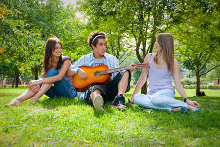 girl bonding: Guy playing guitar in the park, next to him sat two beautiful girls Stock Photo