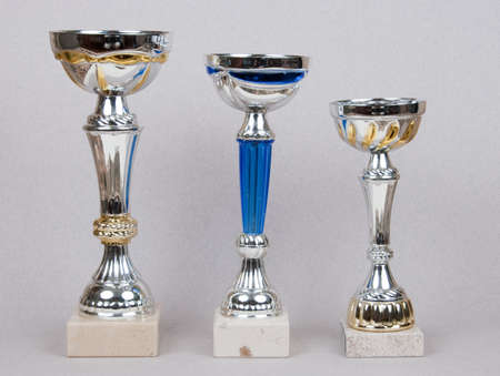 champ: Three prize cup over grey background in studio Stock Photo