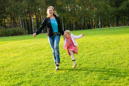 Young mother and daughter playing in the park photo
