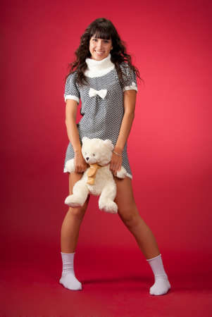 Beautiful young woman with Teddy bear portrait in studio over red background photo
