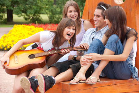 teens playing: Four young  friends play the guitar and laughing outdoors