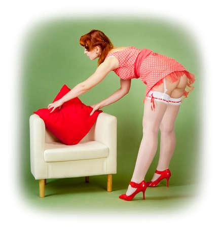 ピンナップ スタイルの女の子が椅子の上に枕を調整します   写真素材