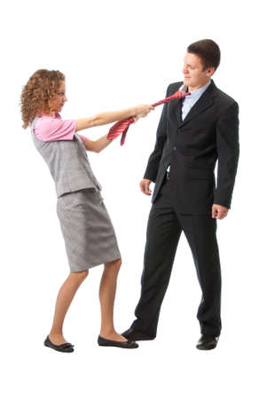 Girl pulls a man in a tie. Isolated over white photo
