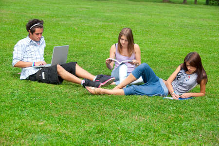 Three students studying outdoors in the park photo