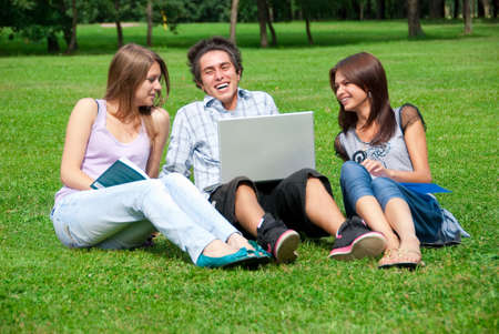 Three students relax and laughing on the grass in the park photo