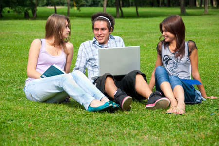 Three students relax and talking on the grass in the park photo