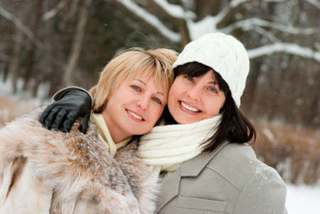 Two happy middle-aged women in winter nature photo