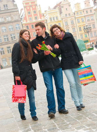 Three happy friends on a street with shopping bags and flowers photo
