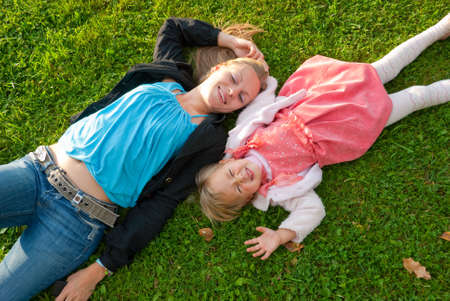 Happy mother and daughter lying on the grass in the park photo