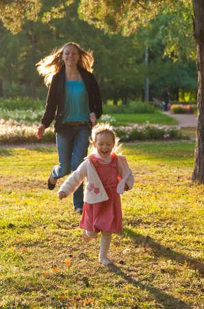 Jovem mãe e filha brincando no parque de verão