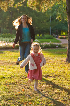 Young mother and daughter playing in the summer park