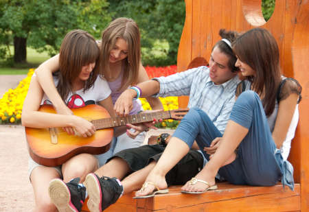 Four young  friends play the guitar and laughing outdoors