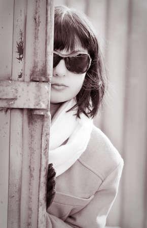 private investigator: Mature woman in sunglasses watching someone. Retro style.