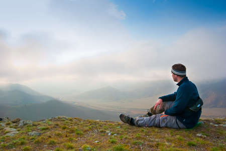 Hiker sits on a peak and enjoy the scenery Stock Photo